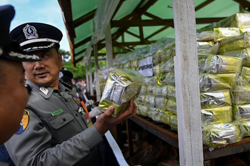 "A Myanmar police official holds a pack of drugs before burning during a destruction ceremony to mark the UN's ""International Day against Drug Abuse and Illicit Trafficking"" in Yangon on June 26, 2019. (Photo by Ye Aung THU / AFP) (Photo credit should read YE AUNG THU/AFP/Getty Images)"