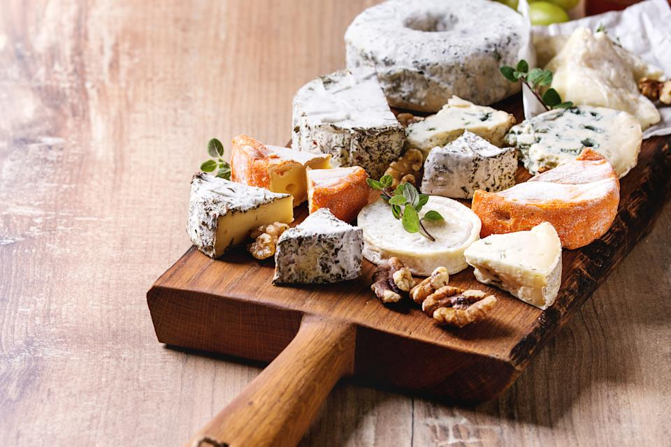 Cheese plate assortment of french cheese served with honey, walnuts, bread and grapes on rustic wooden serving board over wood texture background Close up. (Photo by: Natasha Breen/REDA&CO/Universal Images Group via Getty Images)