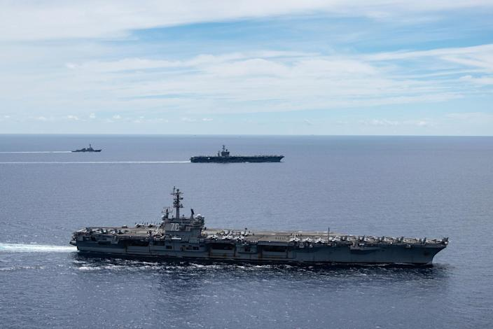 In this July 6, 2020, photo provided by the U.S. Navy, the USS Ronald Reagan (CVN 76, front) and USS Nimitz (CVN 68, rear) Carrier Strike Groups sail together in formation, in the South China Sea