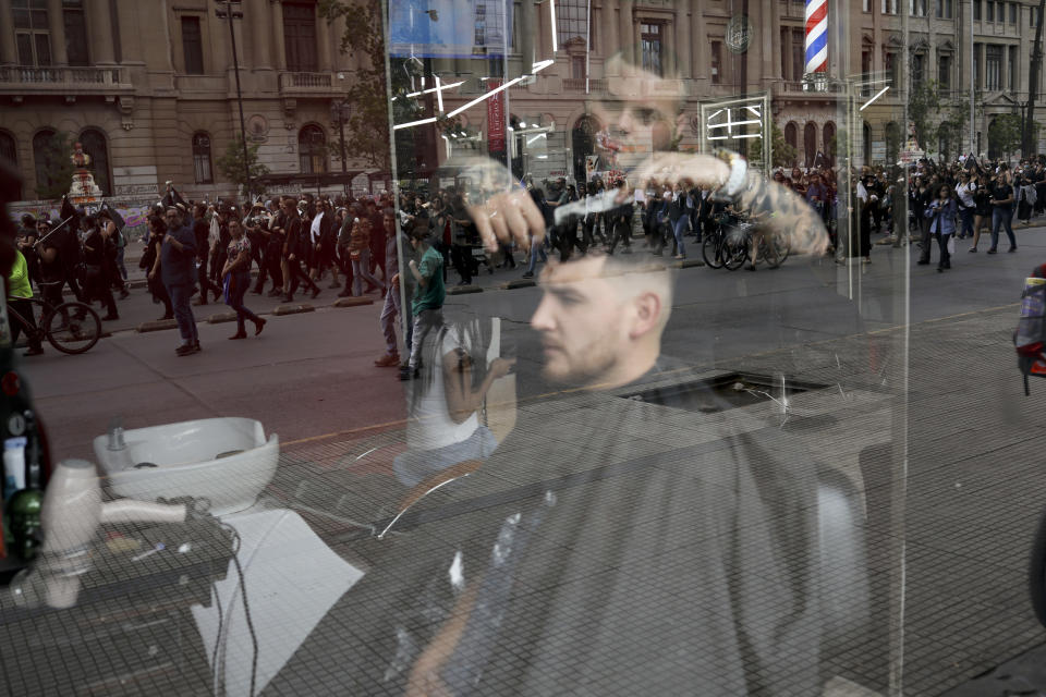 Anti-government demonstrators are reflected in the window of a hairdressing salon in Santiago, Chile, Friday, Nov. 1, 2019. Groups of Chileans continued to protest as government and opposition leaders debated the response to nearly two weeks of protests that have paralyzed much of the capital and forced the cancellation of two major international summits. (AP Photo/Rodrigo Abd)