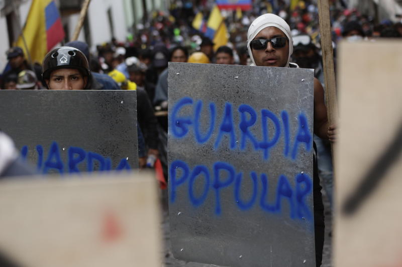 "Anti-government demonstrators march with makeshift shields sprayed painted with the Spanish words for, ""The People's Guard"", during a nationwide strike against President Lenin Moreno and his economic policies, in Quito, Ecuador, Wednesday, Oct. 9, 2019. Ecuador's military has warned people who plan to participate in a national strike over fuel price hikes to avoid acts of violence. The military says it will enforce the law during the planned strike Wednesday, following days of unrest that led Moreno to move government operations from Quito to the port of Guayaquil. (AP Photo/Carlos Noriega)"