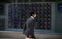 A man wearing protective face mask walks in front of a stock quotation board outside a brokerage in Tokyo