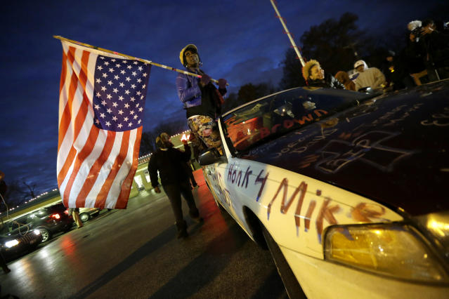 <p>Gina Gowdy holds an upside-down American flag Monday, Nov. 24, 2014, in Ferguson, Mo., more than three months after an unarmed black 18-year-old man was shot and killed there by a white policeman. Ferguson and the St. Louis region are on edge in anticipation of the announcement by a grand jury whether to criminally charge Officer Darren Wilson in the killing of 18-year-old Michael Brown. (AP Photo/Charlie Riedel) </p>