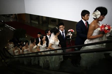 Couples take an escalator as they participate in a staged mass wedding, organised as part of a matchmaking event to inspire singles to get married, at a suburban area of Shanghai in this May 18, 2013 file photo. REUTERS/Carlos Barria