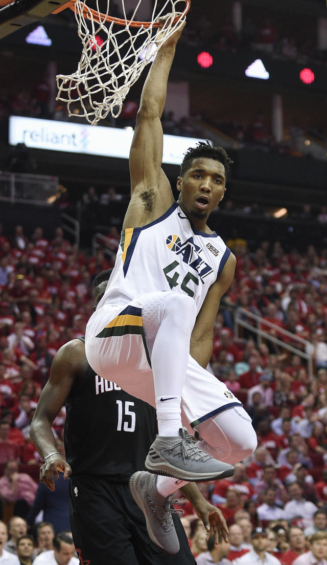 Donovan Mitchell hangs from the rim after his stunning put-back dunk in Utah's Game 2 win. (AP Photo/Eric Christian Smith)