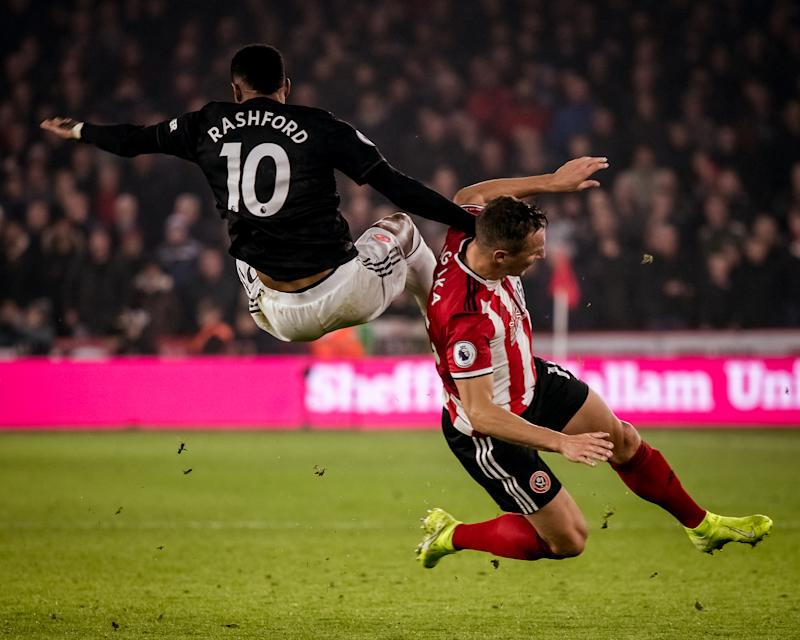 Manchester United's Marcus Rashford (10) collides with Sheffield United's Phil Jagielka on Sunday at Bramall Lane. (Photo by Ash Donelon/Manchester United via Getty Images)