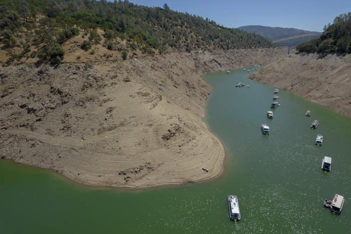 """<div class=""""inline-image__caption""""><p>Steep banks marked with previous water lines surround boats on Oroville Lake during low water levels in Oroville, California, U.S., on Tuesday, June 22, 2021. </p></div> <div class=""""inline-image__credit"""">Kyle Grillot/Bloomberg via Getty</div>"""