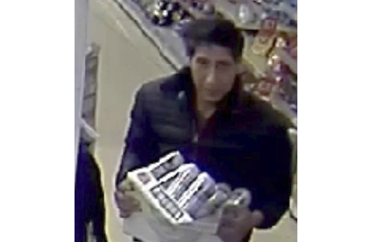 """In this undated photo released Wednesday Oct. 24, 2018, by Britain's Blackpool Police, showing an alleged thief bearing a striking resemblance to Ross Geller, the character played by actor David Schwimmer on the TV show """"Friends."""" Blackpool police posted surveillance-camera footage asking for witnesses to identify their suspect, and thousands of social media users highlighted the suspect's likeness to Schwimmer's US sitcom character. The actor then responded with a Twitter video that shows him scuttling furtively through a convenience store clutching a carton of beer, and Schwimmer wrote: """"Officers, I swear it wasn't me. As you can see, I was in New York."""" and he wished police well with the investigation. The Police have said Schwimmer is not part of their investigation, confirming that """"David Schwimmer was in America on this date."""" (Blackpool Police via AP)"""