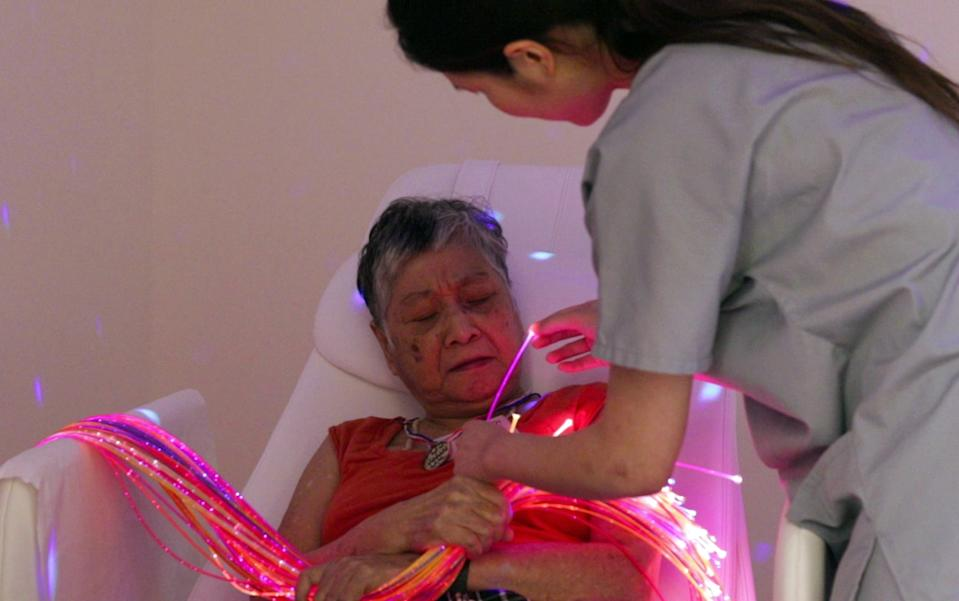 Guided by her therapist, Orange Valley Balestier Care Centre dementia resident Chua Mui Noi, 69, identifies the colours on fibre optic strands in a multi-sensory room. (PHOTO: Yahoo News Singapore)