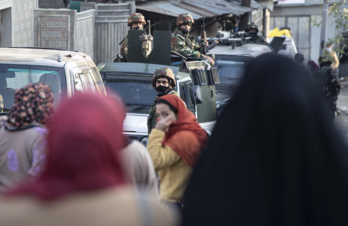 Kashmiri women walk past Indian security officers keeping guard near the site of an attack on the outskirts of Srinagar, Indian controlled Kashmir, Thursday, Nov. 26, 2020. Anti-India rebels in Indian-controlled Kashmir Thursday killed two soldiers in an attack in the disputed region's main city, the Indian army said.(AP Photo/Mukhtar Khan)