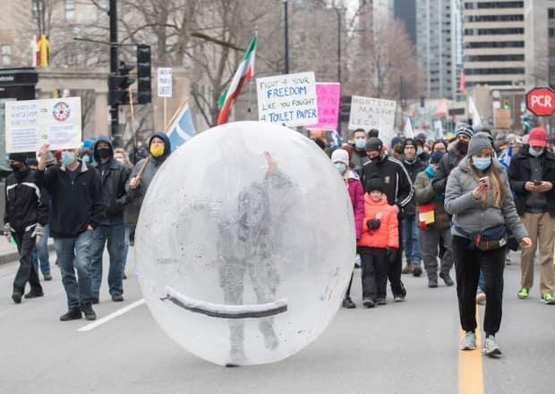 A demonstrator marches inside a plastic ball during a weekend protest in Montreal against the Quebec government's public health measures to curb the spread of COVID-19.