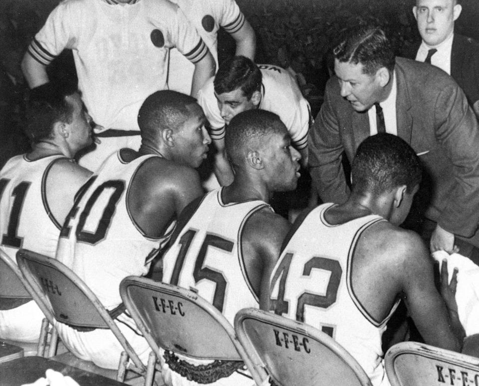 Loyola coach George Ireland, middle right, bends over to coach his team that was trailing Cincinnati in the final of the National Collegiate basketball championship in 1963 at Louisville, Ky. Players, from left to right, are: John Egan, Vic Rouse, Jerry Harkness and Ron Miller.  (AP Photo/File)