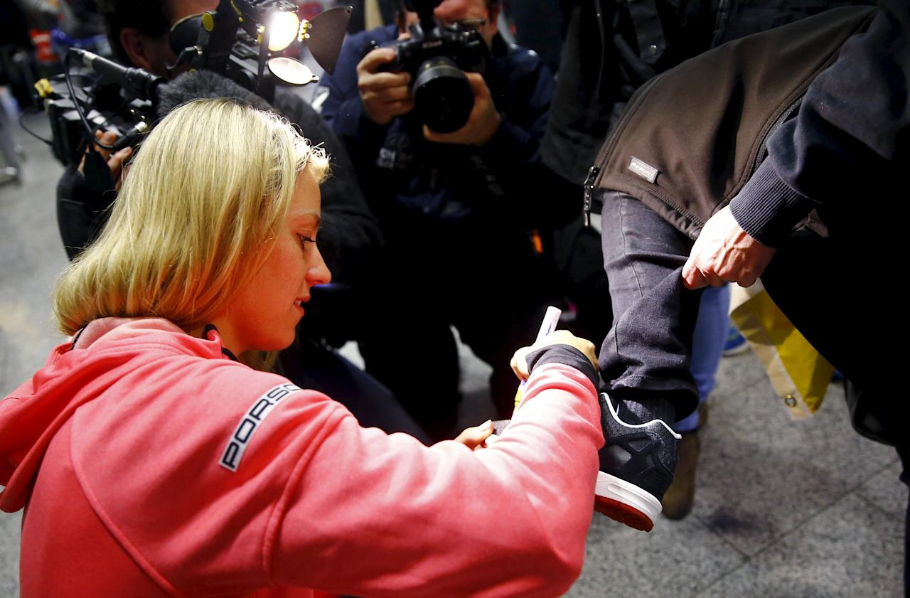 Australian Open winner Angelique Kerber of Germany signs the shoe of a supporter after her arrival at the airport in Frankfurt, Germany