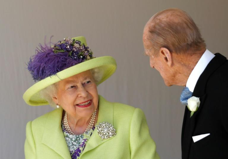 Queen Elizabeth II talks with Prince Philip as they leave after attending the wedding