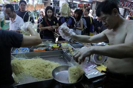 People shop for vegetarian food at a market in Chinatown Bangkok, Thailand, October 19, 2017. Picture taken October 19, 2017. REUTERS/Athit Perawongmetha