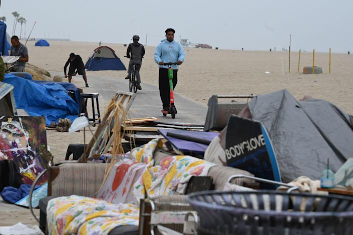 A man rides a scooter past tents as authorities prepare to begin clearing homeless encampments at the Venice Beach Boardwalk on July 2, 2021 in Los Angeles (AFP via Getty Images)