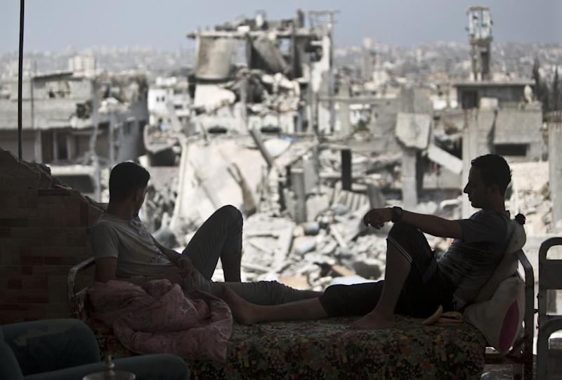 Palestinians sit inside their destroyed house after returning home in the Tufah neighbourhood in eastern Gaza City on August 31, 2014 (AFP Photo/Mahmud Hams)