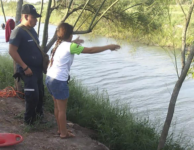 In this Sunday, June 23, 2019 photo, Tania Vanessa Ávalos of El Salvador speaks with Mexican authorities after her husband and nearly two-year-old daughter were swept away by the current while trying to cross the Rio Grande to Brownsville, Texas, in Matamoros, Mexico. Their bodies, the toddler still tucked into her father's shirt with her arm loosely draped around him, were discovered Monday morning several hundred yards (meters) from where they had tried to cross. (AP Photo/Julia Le Duc)