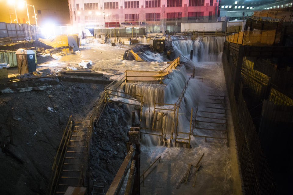 FILE - In this Oct. 29, 2012 file photo, sea water floods the World Trade Center construction site in New York during Superstorm Sandy. A study released in the journal Nature Communications on Tuesday, May 18, 2021, says climate change added $8 billion to the massive costs of 2012's Superstorm Sandy. (AP Photo/John Minchillo, File)