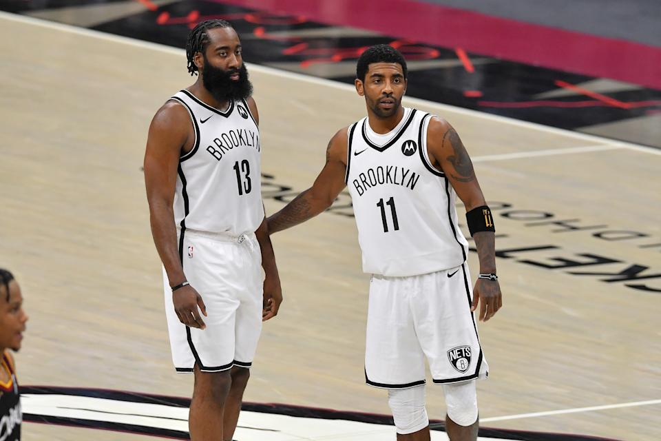 James Harden and Kyrie Irving stand together on the court during a Brooklyn Nets game.
