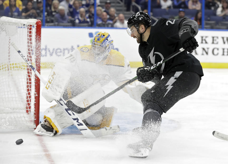 Tampa Bay Lightning right wing Luke Witkowski (28) loses control of the puck as he moves in on Nashville Predators goaltender Juuse Saros (74) during the second period of an NHL hockey game Saturday, Oct. 26, 2019, in Tampa, Fla. (AP Photo/Chris O'Meara)