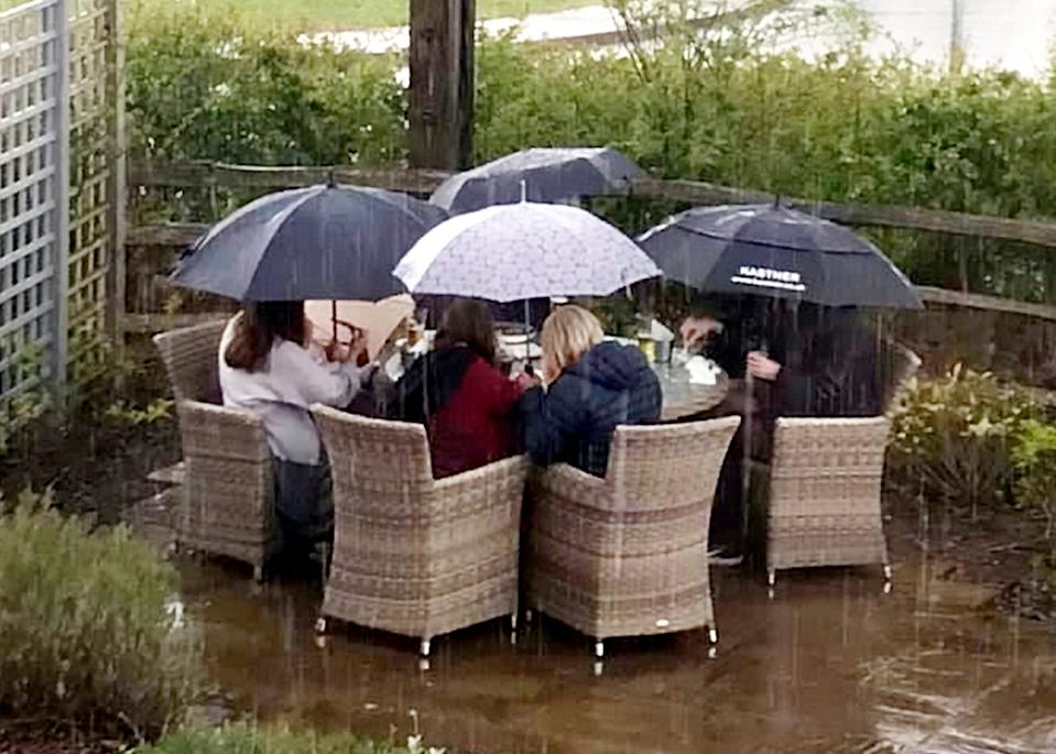 A group of hardy pub goers have raised a smile after being pictured enjoying an outdoor pint - in the pouring rain.  See SWNS story SWPLpub.  The comical photo shows eager drinkers huddled under umbrellas in a beer garden and not letting the wet weather get in the way of their Bank Holiday weekend celebrations.  It was taken yesterday (May 1) outside The Cranberry Farm pub, in Exeter, Devon, and has been hailed as a true sign of British grit.  The pub, owned by Hall and Woodhouse brewery, opened again for outdoor service last Thursday (April 29).