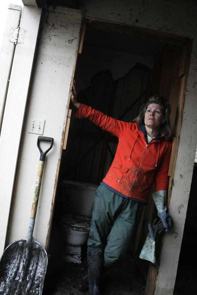 <p>Debbie Mones takes a break from shoveling mud and oil out of the backyard shed of her home, which was severely damaged by flooding during Hurricane Katrina, in Chalmette, La., east of New Orleans, Dec. 17, 2005. (Photo: Jacqueline Larma/AP) </p>