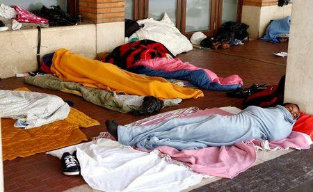 Migrants sleep under blankets in a makeshift camp at the San Giovanni railway station in Como