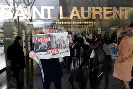 "Activists hold placards which read ""Sexist"" during a demonstration in front of a Yves Saint Laurent shop in Paris, France, March 7, 2017. REUTERS/Philippe Wojazer"