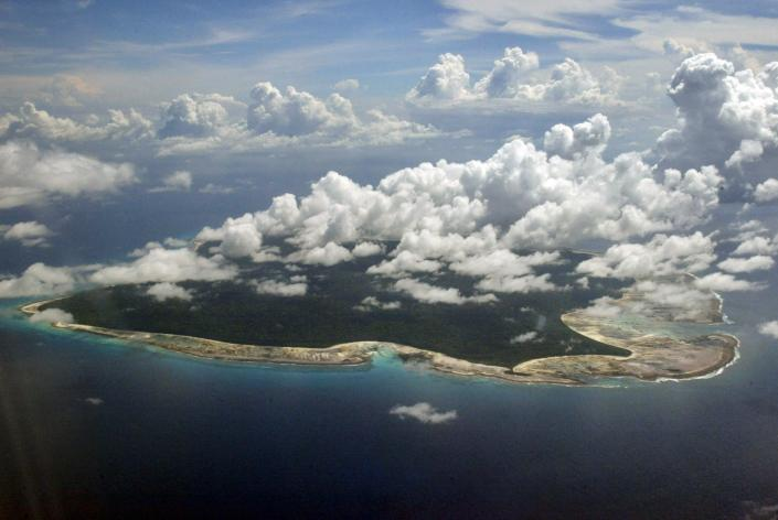 FILE – In this Nov. 14, 2005 file photo, clouds hang over the North Sentinel Island, in India's southeastern Andaman and Nicobar Islands. India used heat sensors on flights over hundreds of uninhabited Andaman Sea islands Friday, March 14, 2014, and will expand its search for the missing Malaysia Airlines jet farther west into the Bay of Bengal, officials said. The Indian-controlled archipelago that stretches south of Myanmar contains 572 islands covering an area of 720-by-52 kilometers. Only 37 are inhabited, with the rest covered in dense forests. (AP Photo/Gautam Singh, File)