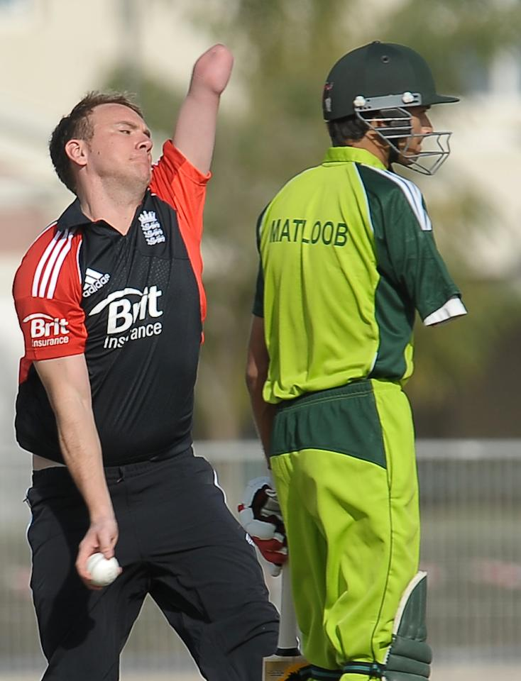 England disabled cricketer Daniel Holder (L) delivers the ball as Pakistan disabled cricketer Matloob Qureshi (R) look on during the T20 match between England Disaballity team and Pakistan Disaballity team at the ICC Global Cricket Academy (ICC GCA) in Dubai Sports City on February 11, 2012. Pakistan beat England in the first-ever Twenty20 match between the physically challenged cricket teams by 14 runs. AFP PHOTO/ LAKRUWAN WANNIARACHCHI (Photo credit should read LAKRUWAN WANNIARACHCHI/AFP/Getty Images)