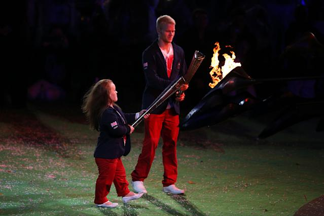 LONDON, ENGLAND - SEPTEMBER 09: Swimmer Eleanor Simmonds and athlete Jonnie Peacock of Great Britain light torches from the flame of the Paralympic cauldron as it is extinguished during the closing ceremony on day 11 of the London 2012 Paralympic Games at Olympic Stadium on September 9, 2012 in London, England. (Photo by Hannah Johnston/Getty Images)