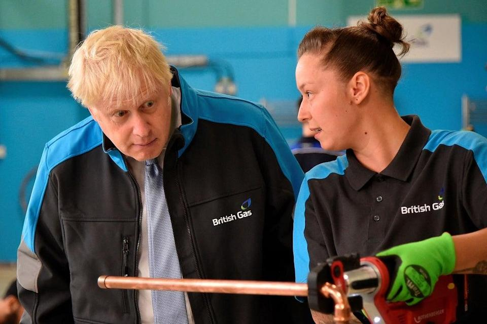 Boris Johnson listens to apprentice Amy Gray during a visit to a British Gas training academy near Leicester, on Monday   (POOL/AFP via Getty Images)