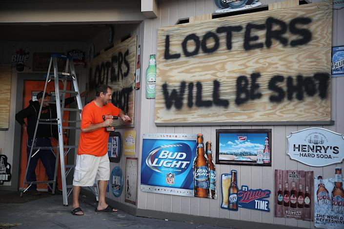 <p>Doug Lewis (L) and Chris Williams use plywood with the words 'Looters will be shot' to cover the windows of Knuckleheads bar as they try to protect the business ahead of the arrival of Hurricane Florence on Sept. 12, 2018 in Myrtle Beach, S.C. (Photo: Joe Raedle/Getty Images) </p>
