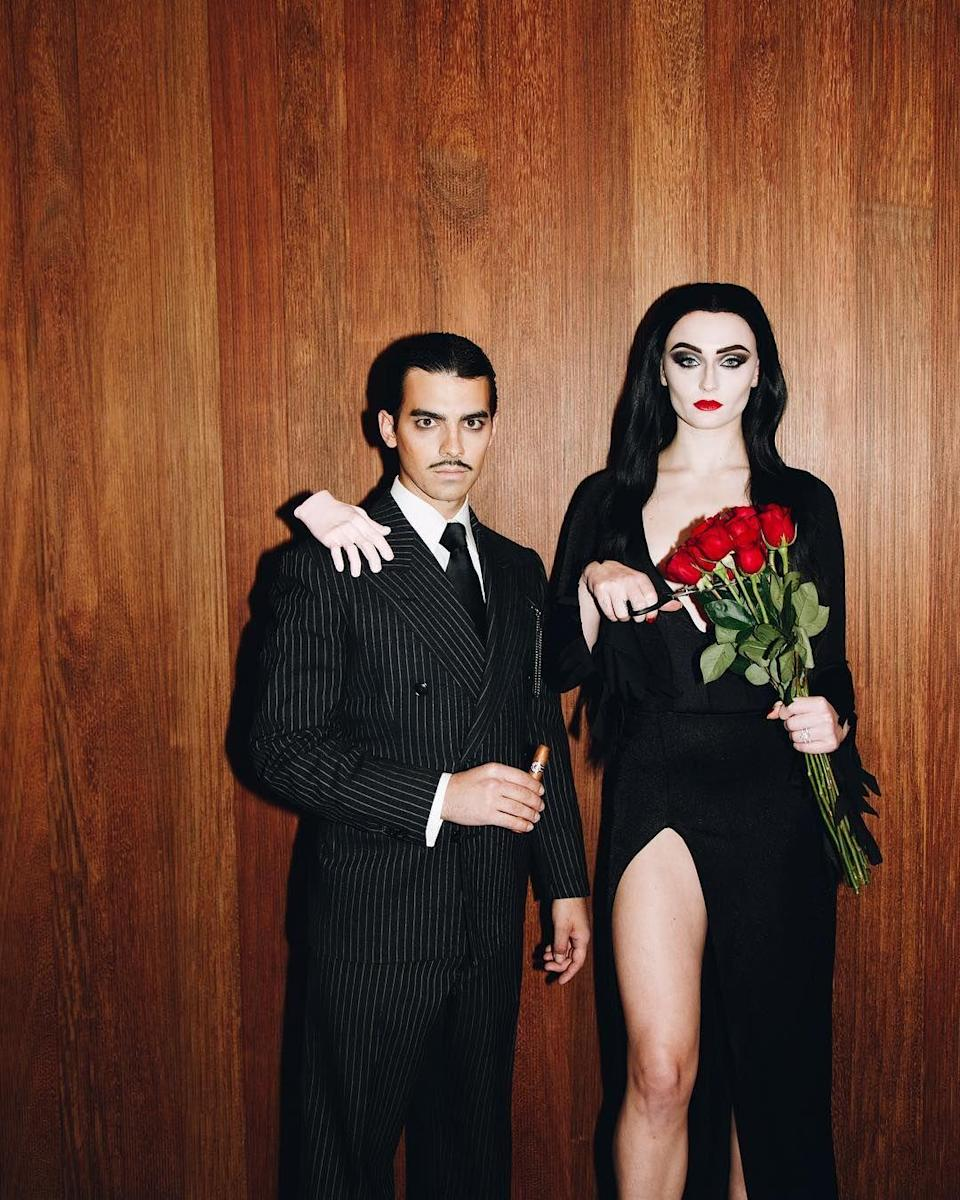 "<p>The newlyweds perfectly executed the ""all together ooky"" parents of the <a href=""https://www.goodhousekeeping.com/holidays/halloween-ideas/g28589490/best-wednesday-addams-costume-ideas/"" rel=""nofollow noopener"" target=""_blank"" data-ylk=""slk:Addams family"" class=""link rapid-noclick-resp"">Addams family</a>. They even managed to include Thing in their costume!</p>"