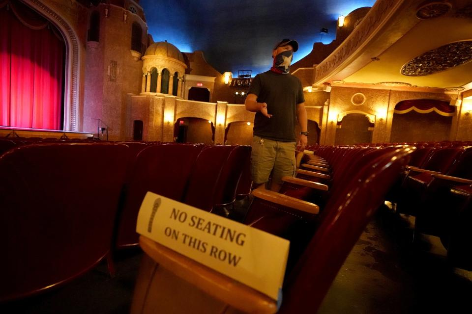 Employee Grayson Allred responds to questions from a reporter while standing inside the Paramount Theatre on Wednesday, Dec. 16, 2020, in Abilene, Texas. The theatre has closed down indefinitely due to rising cases of COVID-19 in the city. (AP Photo/Tony Gutierrez)