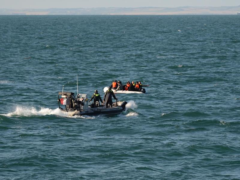 Rescuers reach a group of migrants in the English Channel on Saturday: PA