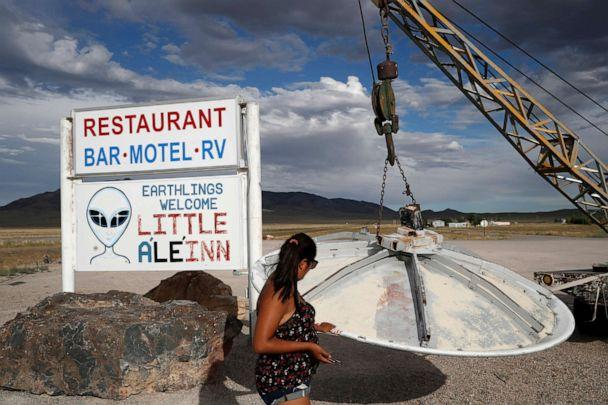 PHOTO: Grace Capati looks at a UFO display outside of the Little A'Le'Inn, in Rachel, Nev., the closest town to Area 51, July 22, 2019. (John Locher/AP, FILE)