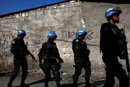 U.N. peacekeepers walk along a street during a patrol with Haitian national police officers and members of UNPOL (United Nations Police) in the neighborhood of Cite Soleil, in Port-au-Prince