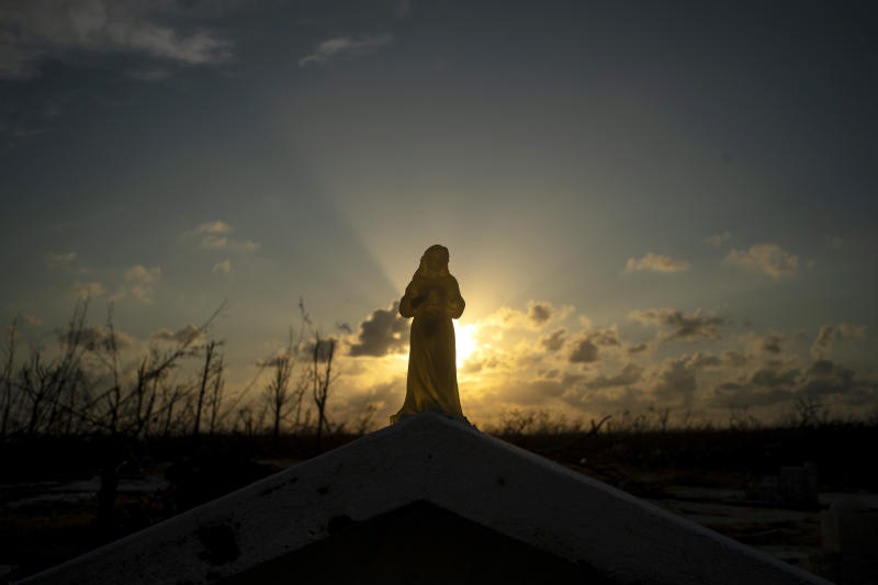 The sun sets behind a statuette of the Virgin Mary atop a grave broken by the force of Hurricane Dorian, in the cemetery of Mclean's Town, Grand Bahama, Bahamas, Wednesday Sept. 11, 2019. Bahamians are tackling a massive clean-up a week after Hurricane Dorian devastated the archipelago's northern islands. Residents sift through debris as they try to save prized possessions and prepare to rebuild from one of the strongest Atlantic hurricanes in history. (AP Photo/Ramon Espinosa)