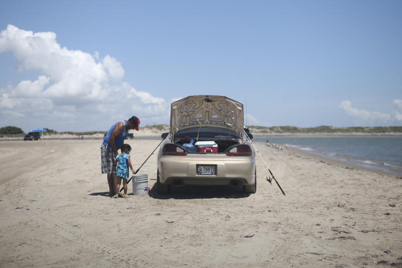 In this Aug. 3, 2019 photo, a child watches a grown up clean a fish during a fishing trip to Playa Bagdad near the border city of Matamoros, Mexico. Playa Bagdad appeared on maps in 1848, when the border was drawn during the Mexico-American War. (AP Photo/Emilio Espejel)