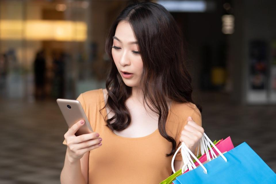 Woman looking at her phone while shopping at the mall