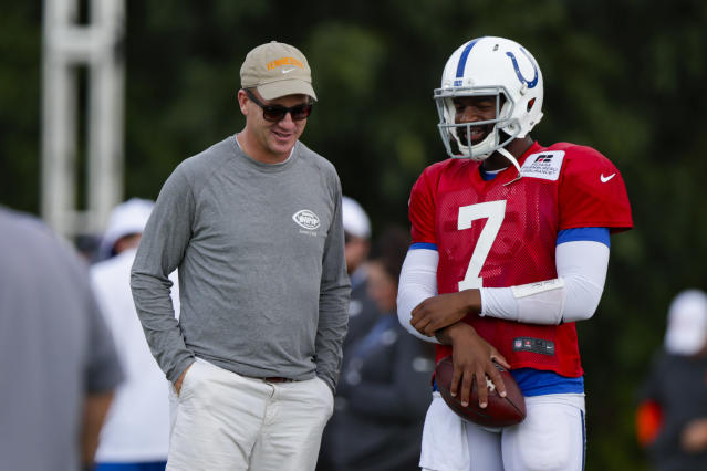 Indianapolis Colts quarterback Jacoby Brissett (7) talks with former Colts quarterback Peyton Manning during practice at the NFL team's football training camp in Westfield, Ind., Thursday, Aug. 15, 2019. The Colts held a joint practice with the Cleveland Browns. (AP Photo/Michael Conroy)