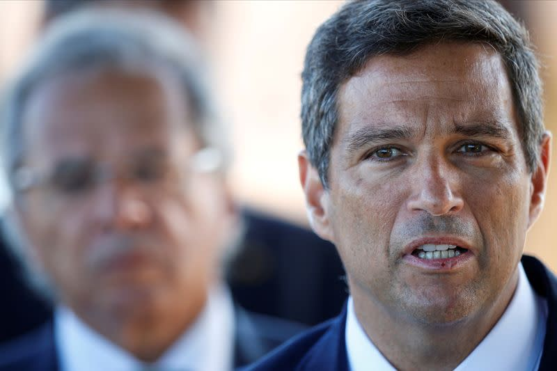 FILE PHOTO: Brazil's Central Bank President Roberto Campos Neto speaks near Brazil's Economy Minister Paulo Guedes while leaving Alvorada Palace in Brasilia