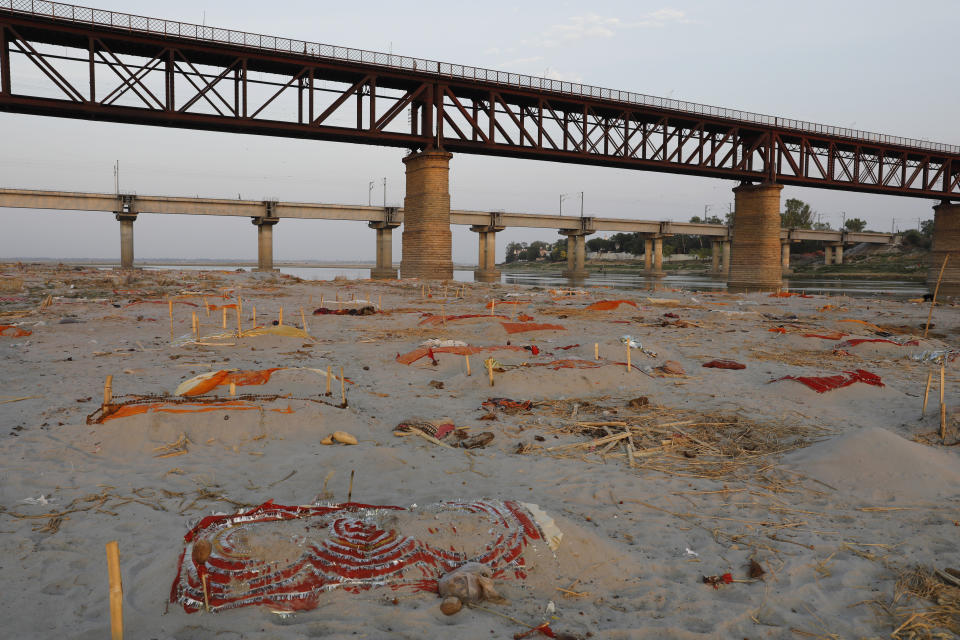 Bodies are seen under colourful cloth on the banks of Ganges River.