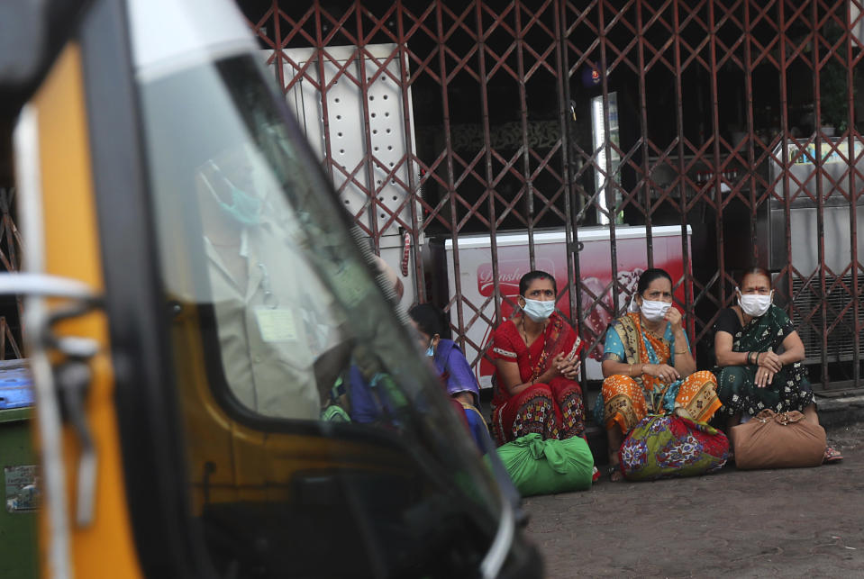 A group of women wearing face masks as a precaution against the coronavirus waits for transport in Dharavi, one of Asia's biggest slums, in Mumbai, India, Wednesday, Dec. 30, 2020. India's confirmed coronavirus cases have crossed 10 million with new infections dipping to their lowest levels in three months, as the country prepares for a massive COVID-19 vaccination in the new year. (AP Photo/Rafiq Maqbool)
