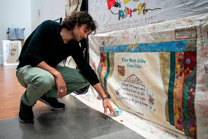 Huston Ochoa, 33, looks at a quilt panel his family made which is part of the AIDS Memorial Quilt that is on display as part of the exhibit, A Matter of Time: Examining Forty Years of AIDS While Living through a Pandemic, at the Coral Gables Museum in Miami, Florida on Monday, April 5, 2021. OchoaÕs family made the quilt panel in honor of his mother and father who both died of AIDS when he was a young boy.