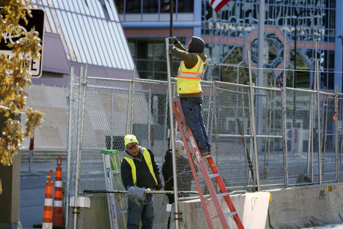 Workers install barbed wire on fencing outside the Hennepin County Government Center, Wednesday, Feb. 23, 2021 in Minneapolis, as part of security preparation for the trial of former Minneapolis police officer Derek Chauvin. The trial is slated begin with jury selection on March 8. Chauvin is charged with murder the death of George Floyd during an arrest last May in Minneapolis. (AP Photo/Jim Mone)