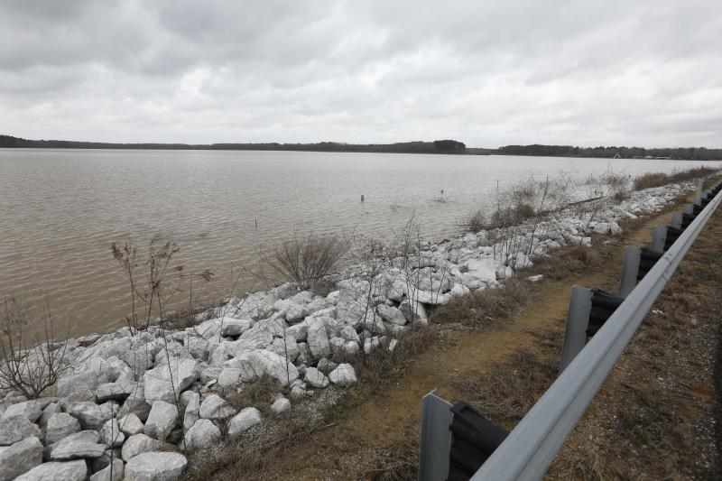 Darkening skies surround the Oktibbeha County Lake near Starkville, Miss., Wednesday, Jan. 15, 2020. The rain-swollen lake is keeping heavy pressure on a dam that is in danger of failing, state and local officials said Wednesday. A breach would affect an estimated 130 properties and nine highways. (AP Photo/Rogelio V. Solis)