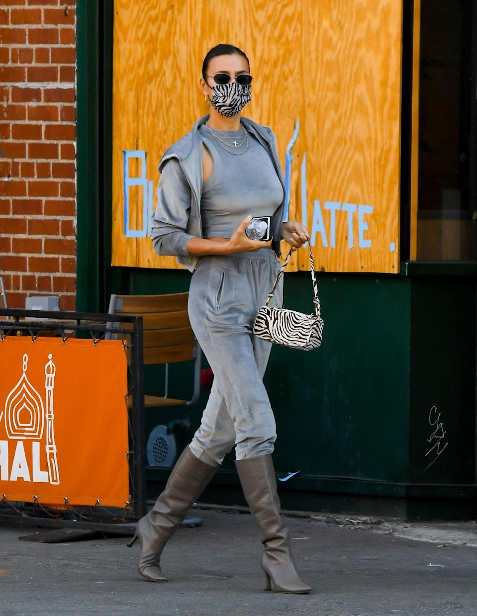"""<p>The supermodel was spotted running errands and picking up coffee in New York City on November 9 wearing the comfiest of outfits during the pandemic.</p><p>The 34-year-old wore a grey velour tracksuit from <a href=""""https://www.elle.com/uk/life-and-culture/g34434604/kim-kardashian-career/"""" rel=""""nofollow noopener"""" target=""""_blank"""" data-ylk=""""slk:Kim Kardashian"""" class=""""link rapid-noclick-resp"""">Kim Kardashian</a>'s shapewear brand <a href=""""https://www.elle.com/uk/life-and-culture/culture/a33940186/kim-kardashian-homeware-interiors-business/"""" rel=""""nofollow noopener"""" target=""""_blank"""" data-ylk=""""slk:SKIMS"""" class=""""link rapid-noclick-resp"""">SKIMS</a> which consisted of a <a href=""""https://skims.com/products/velour-hoodie-smoke"""" rel=""""nofollow noopener"""" target=""""_blank"""" data-ylk=""""slk:hoodie"""" class=""""link rapid-noclick-resp"""">hoodie</a>, <a href=""""https://skims.com/products/velour-crew-neck-tank-smoke"""" rel=""""nofollow noopener"""" target=""""_blank"""" data-ylk=""""slk:crew neck vest top"""" class=""""link rapid-noclick-resp"""">crew neck vest top</a> and jogging <a href=""""https://skims.com/products/velour-jogger-smoke"""" rel=""""nofollow noopener"""" target=""""_blank"""" data-ylk=""""slk:bottoms"""" class=""""link rapid-noclick-resp"""">bottoms</a>. She teamed the look with a zebra-print mask and matching printed handbag, black sunglasses and grey pointed knee-high boots.</p><p><a class=""""link rapid-noclick-resp"""" href=""""https://go.redirectingat.com?id=127X1599956&url=https%3A%2F%2Fwww.marksandspencer.com%2Fpure-cashmere-textured-joggers%2Fp%2Fclp60459655%3Fcolor%3DGREYMIX&sref=https%3A%2F%2Fwww.elle.com%2Fuk%2Ffashion%2Fcelebrity-style%2Fg34359706%2Firina-shayk-style-file%2F"""" rel=""""nofollow noopener"""" target=""""_blank"""" data-ylk=""""slk:SHOP GREY CASHMERE JOGGERS"""">SHOP GREY CASHMERE JOGGERS</a></p><p><a class=""""link rapid-noclick-resp"""" href=""""https://go.redirectingat.com?id=127X1599956&url=https%3A%2F%2Fwww.net-a-porter.com%2Fen-gb%2Fshop%2Fproduct%2Fgianvito-rossi%2F85-suede-knee-boots%2F1289482&sref=https%3A%2F%2Fwww.elle.com%2Fuk%2Ffashion%2"""